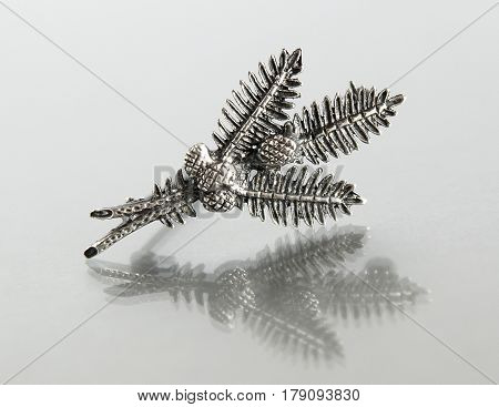 Vintage filigree silver brooch Fir branch and cones on gray background with mirror reflection