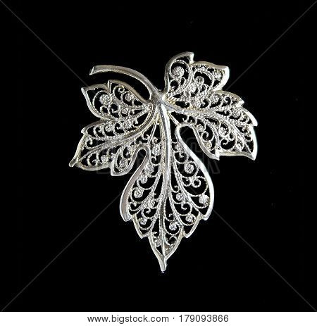 Vintage filigree silver brooch Grape leaf isolated on black background
