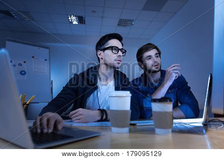 Data privacy. Intelligent genius handsome hackers using the laptop and stealing personal data information while committing a cyber crime