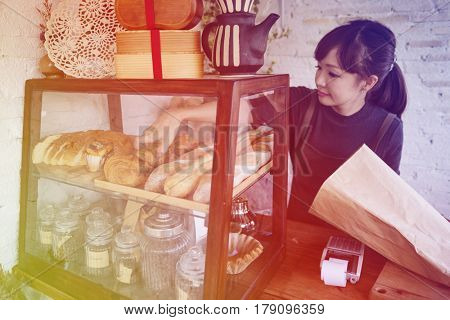 Young patissier woman putting bread pastry on the shelf