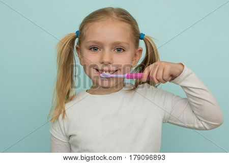 adorable school age girl practicing good oral hygiene brushing teeth