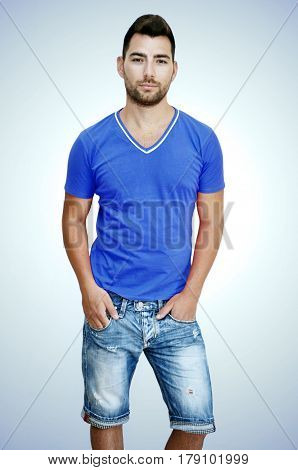 Young man with dark hair and brown eyes wearing knee length light blue jeans and a bright blue T- Shirt, light blue background.