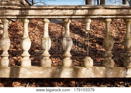 Destroyed balustrade with a sticking armature. Old park. Fallen leaves. Broken balustrade of gray stone.