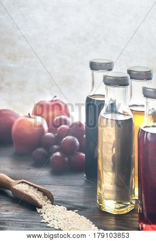 Bottles with different kinds of vinegar on the wooden background poster