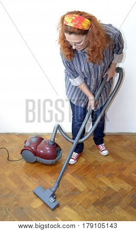 Housewife with vacuum cleaner cleaning floor - view from below