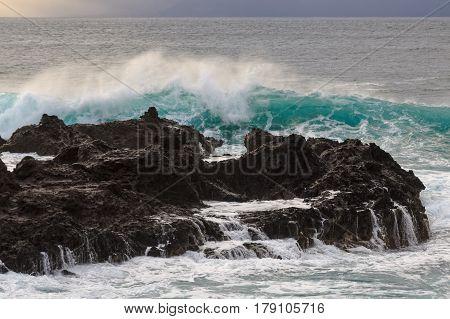Surf splashing against the lava rocks on the North shore of Maui.