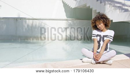 Smiling female wearing sportive t-shirt and knee-high socks sitting with legs crossed on pool background.