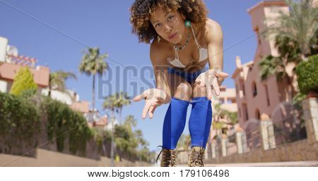 From below shot of fit stylish girl in swimwear and roller skates sending air kiss at camera.