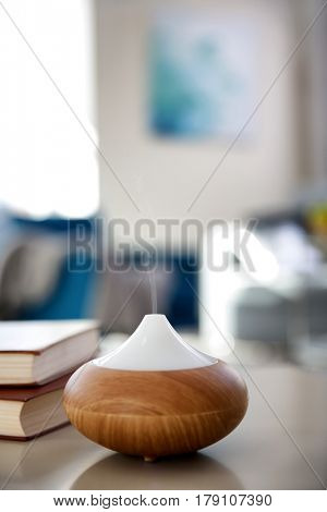 Electric oil diffuser on blurred room background