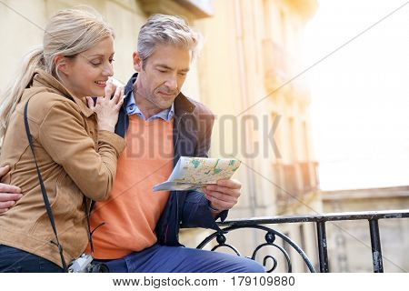 Couple of tourists visiting european city and checking map