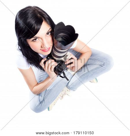 black haired girl sitting on the floor holding a professional dslr camera looking up