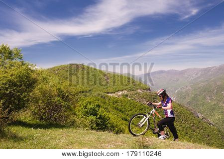 female mountain biker pushing her mountainbike uphill
