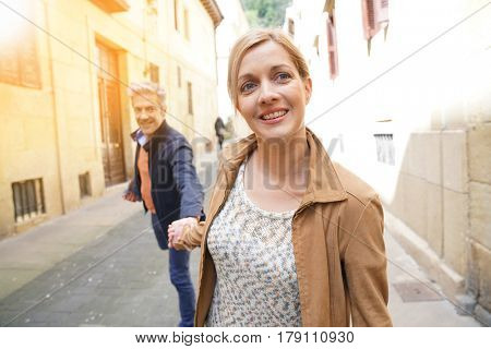 Middle-aged couple walking in street of spanish old quarter