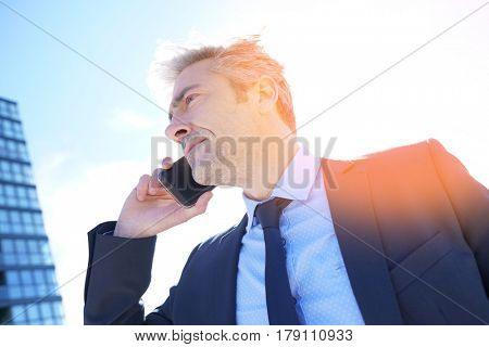 Businessman talking on phone outside the office