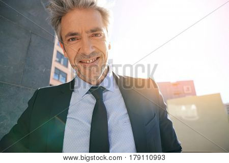 Portrait of businessman waiting outside building, leant on wall