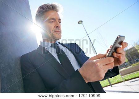 Businessman using pda outside the office