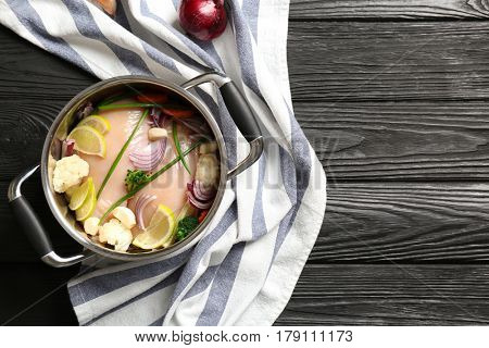 Raw chicken breasts with lemon and vegetables in saucepan