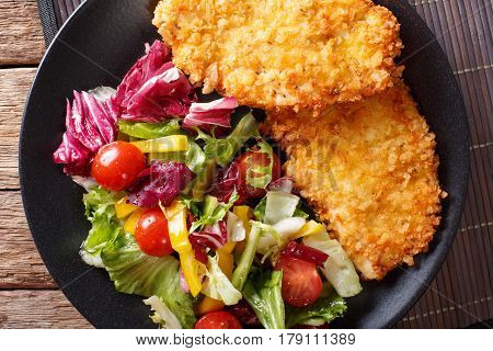 Japanese Steak In Breadcrumbs Panko And Fresh Vegetable Salad Close-up On The Table. Horizontal Top