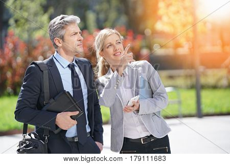 Business people meeting outside and checking building place
