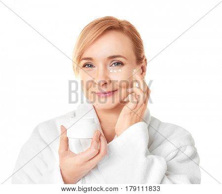 Senior woman applying anti-aging cream on face against white background