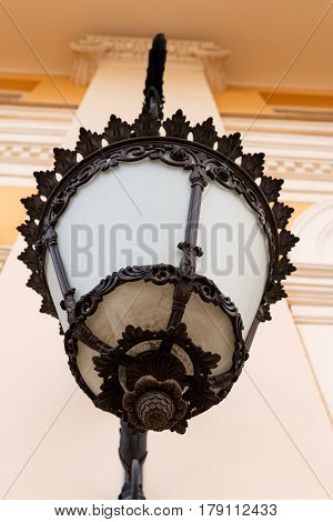 Wrought lantern on the wall of a classical building. Bottom view. Looks like a bumpkin