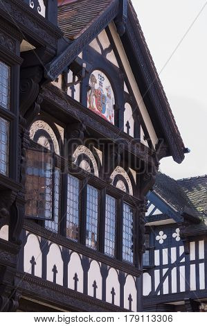 Chester England UK - March 25 2017: Details of ornately carved medieval wooden frame buildings with lead glass windows on Eastgate Street in the historic city of Chester