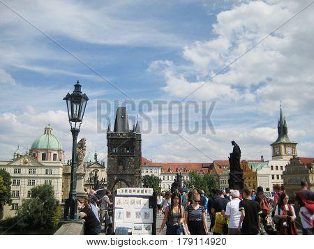 PRAGUE, CZECH REPUBLIC - AUGUST 17, 2016: People walking on Charles Bridge (Czech: Karluv most). Historic famous bridge with tourists, local street painters across travel tourist landmark