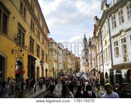 PRAGUE, CZECH REPUBLIC - AUGUST 17, 2016: People walking on Mostecka street near Charles bridge in Prague city center, Czech Republic. Big crowd of people on popular Prague street during summer