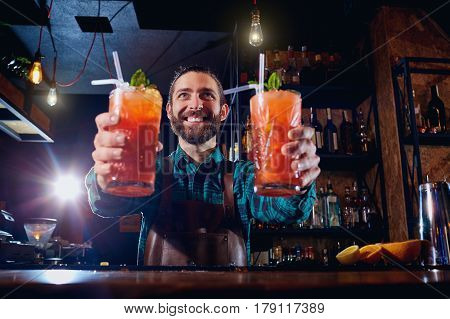 Barman holds out cocktails to  client at the bar in restaurant. Welcome.
