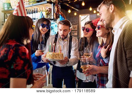 Friends at the birthday party party are celebrating together at bar restaurant.