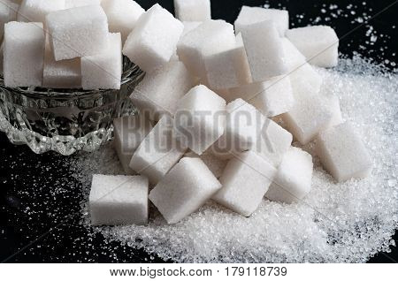 white granulated sugar and refined sugar on black tables surface closeup