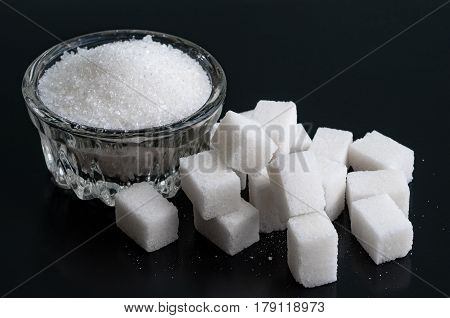 Bowl of white granulated sugar and refined on black surface close-up