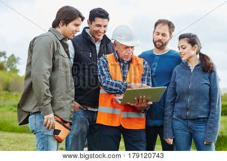 Craftsmen and artisans with laptop computer working and cooperating as team