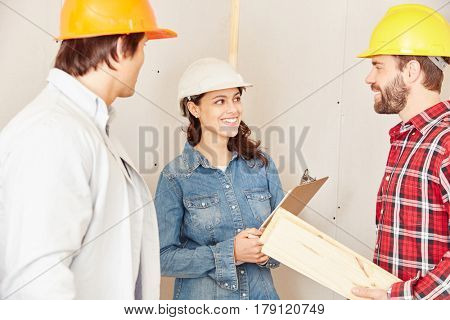 Architect with checklist cooperating with craftsmen