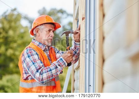 Senior citizen as building construction craftsman working on new house