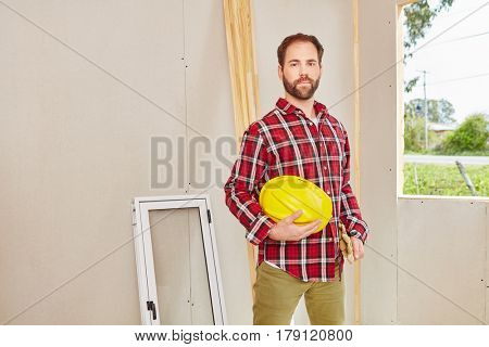 Confident blue collar worker at construction site building house