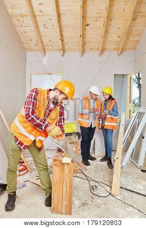 Carpenter cutting wood while artisans plan renovation