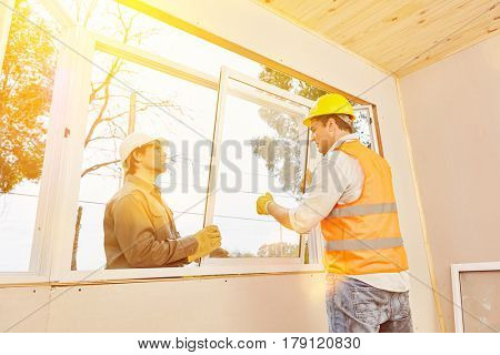 Teamwork between artisan and craftsman installing window
