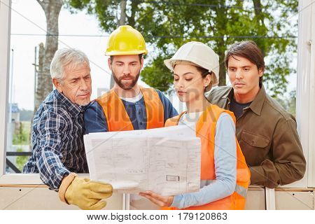 Building construction team planning new house with floorplan