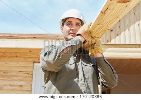 Blue collar worker carrying wood in construction site
