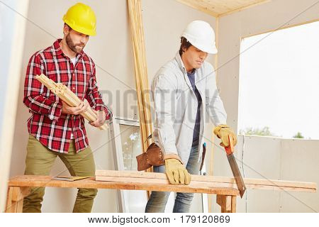Craftsman and carpenter working as a team cutting wood