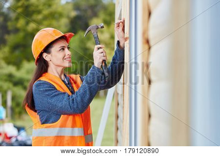 Woman as carpenter apprentice building new house