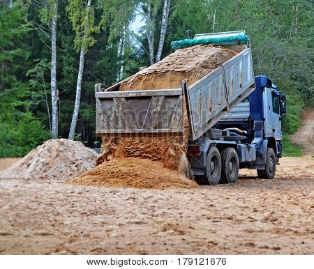 Blue dump truck with hoisted body unloads sand on the building site in rural areas