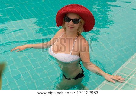 Young woman in a pool at cloudy day