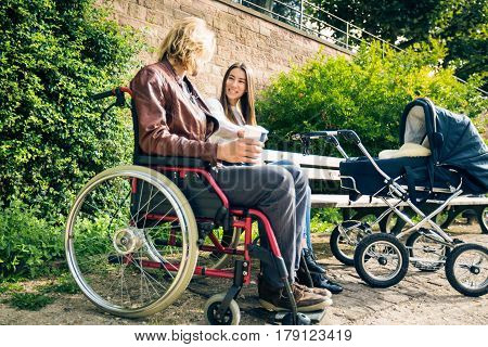 Young parents with father sitting in wheelchair are enjoying time outdoors, taking their baby to a park along the banks of the river Neckar in Heidelberg, Germany.