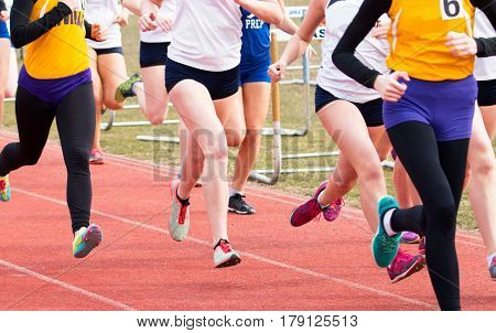 High school girls rae the mile on a red track in the early spring