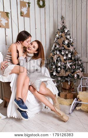 Daughter hugging and kissing her mother near the Christmas tree.