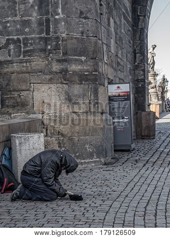 PRAGUE, CZECH REPUBLIC - MARCH 8 2017: Clochard begging for money at the Charles Bridge, Prague, Czech Republic