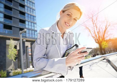 Businesswoman checking meeting schedule on smartphone