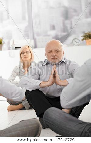 Senior Businessman im Büro mit Kollegen, geschlossenen Augen meditieren.?